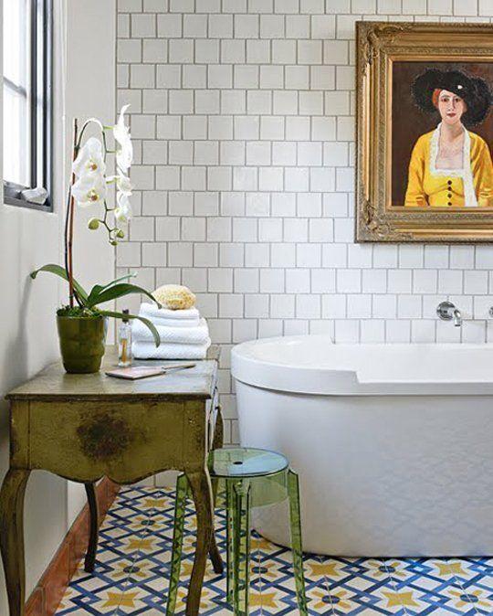 kolorowe płytki cementowe na podłodze w łazience z nowoczesną wanną, plastikowym krześle i stylizowaną szafką