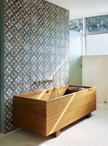 wzorzyste płytki cementowe na ścianie w zestawieniu z drewnianą wanną.