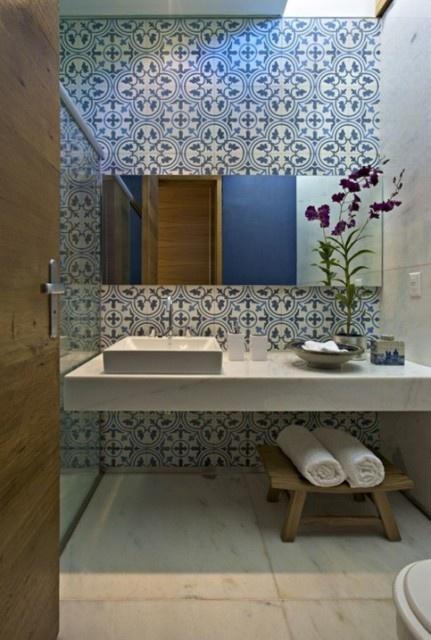 niebieskie geometryczne płytki cementowe na ścianie w łazience.