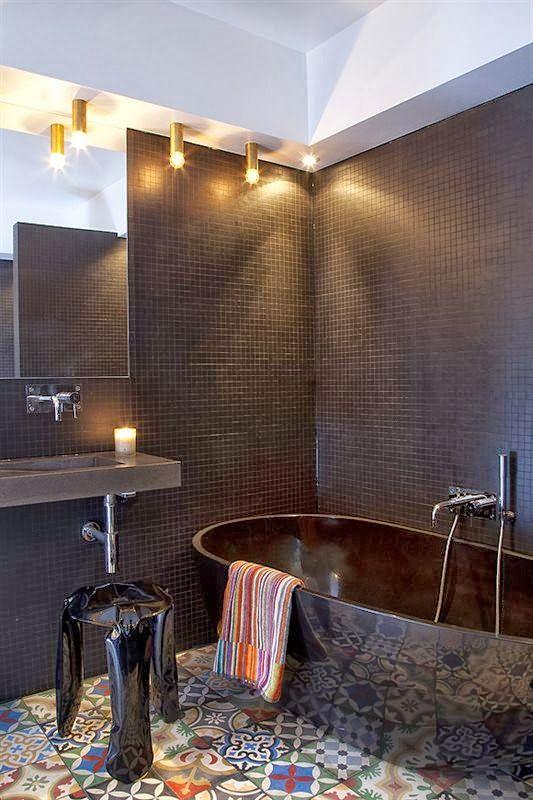 kolorowe płytki cementowe na podłodze w ciemnej łazience z czarną lakierowaną wanną