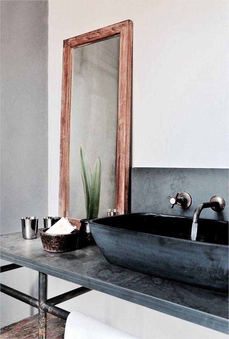 lustro łazienkowe w drewnianej ramie, postawione pionowo na blacie obok umywalki