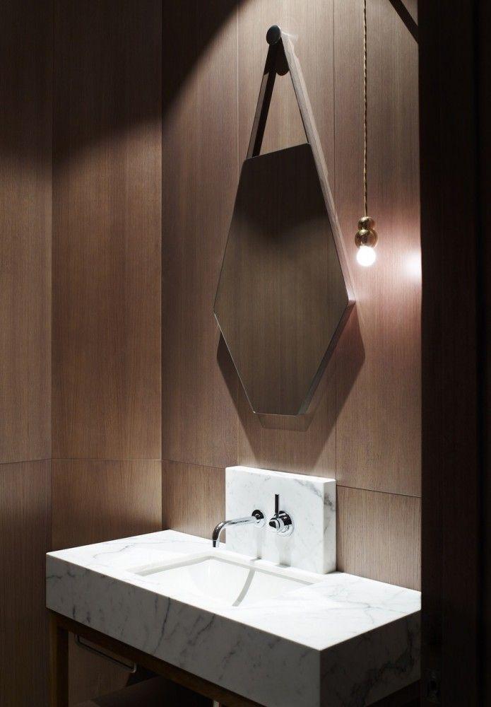 lustro łazienkowe o nietypowym kształcie w łazience wykończonej drewnem