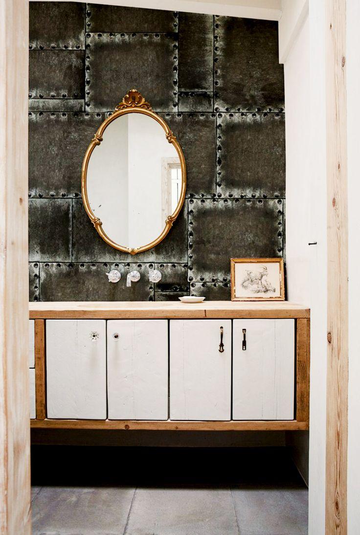 lustro łazienkowe na tle nitowanej ciemnej ściany