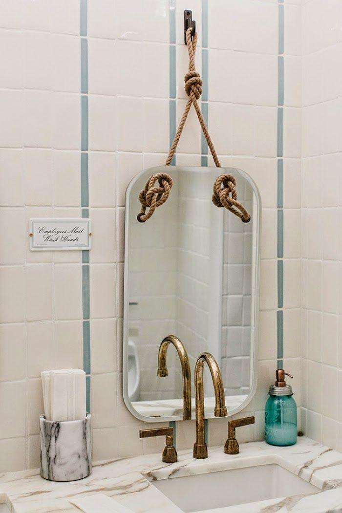 pionowe lustro łazienkowe zawieszone na linie w łazience wykończonej miedzianymi elementami