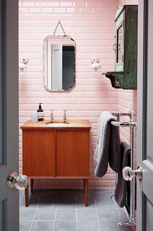 Ozdobnie cięte lustro łazienkowe podwieszone na łańcuchu na szafeczką z umywalką w blacie