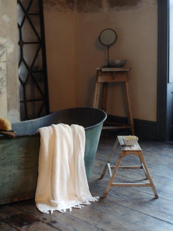 łazienka z wolno stojącą wanną oraz stołek vintage jako pomocnik łazienkowy