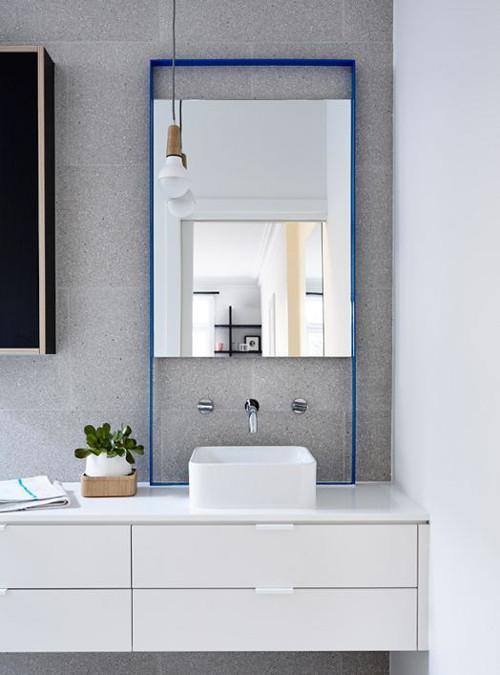 aranżacje łazienki - Surowa kolorystyka łazienki z niebieskim akcentem lustra.