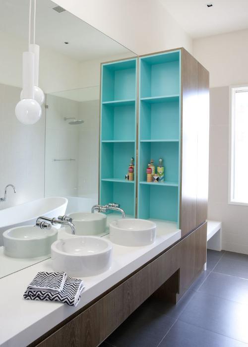 aranżacje łazienki - Miętowy akcent szafki na tle tafli lustra.