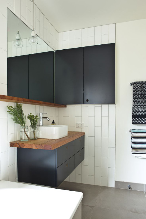aranżacje łazienki, wykończona ciemnymi szafkami oraz drewnem.