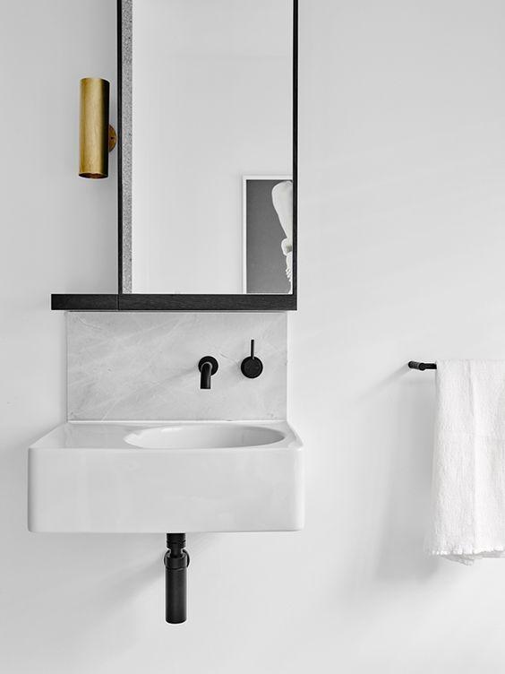 mała biała asymetryczna umywalka z czarną bateria