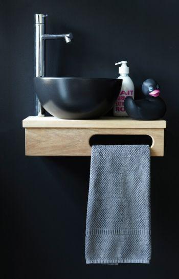 mała czarna umywalka na blacie z uchwytem na ręcznik