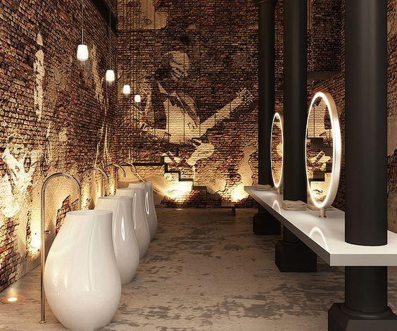 łazienka z ceglaną ścianą pełną grafik połączone z nowoczesnymi umywalkami