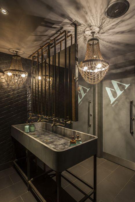 łazienka w stylu industria z barokowymi żyrandolami
