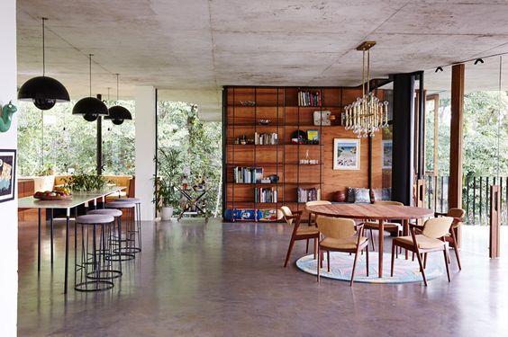 wnętrze domu wyposażone jest lekkie meble, połączenie surowych ścian z drewnem