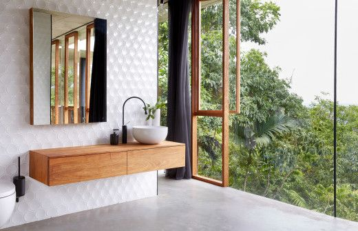 oryginalna umywalka w połączeniu z bateriami w kształcie kropli na podwieszanej drewnianej szafce w kontraście białej o mocnej fakturze ścianie