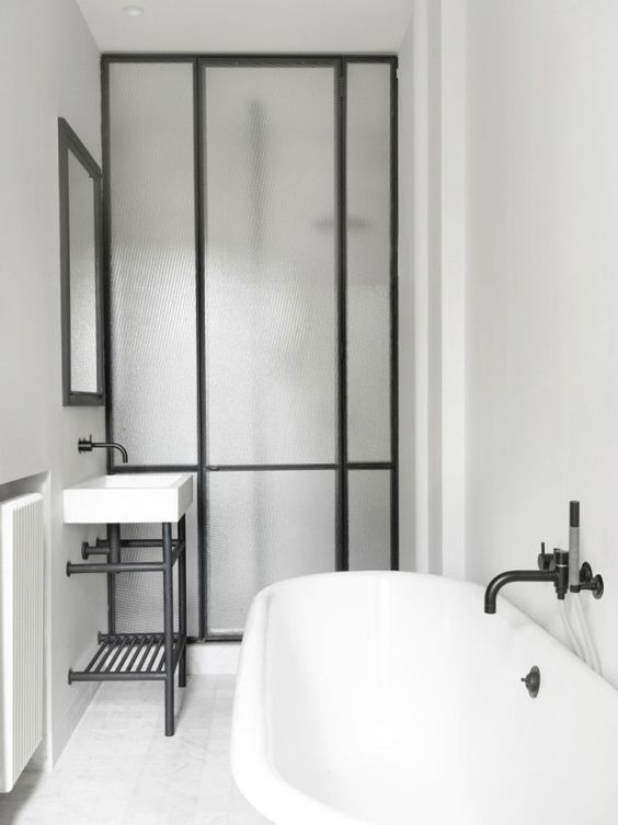 """kabina prysznicowa z drzwiami w czarnej ramie na zawiasach, duże podziały i efekt """"zmrożonej"""" szyby"""