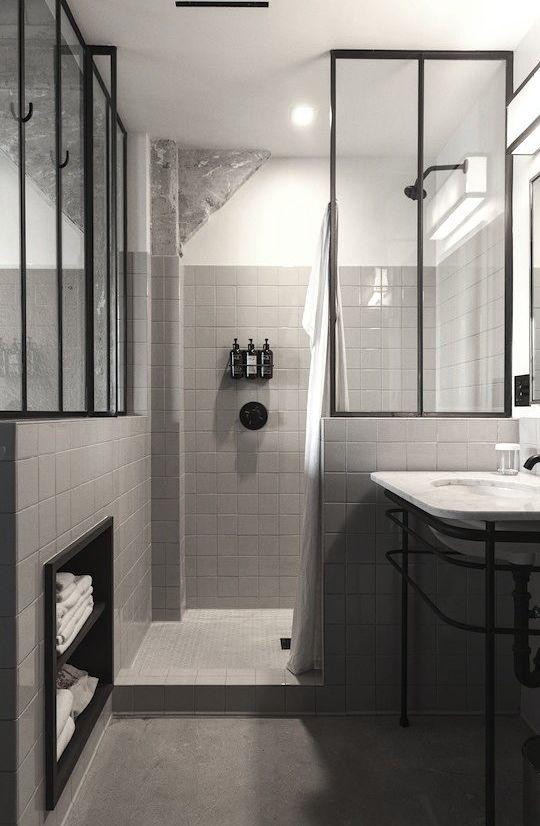 kabina prysznicowa z krótką ścianką zamontowaną na murku obłożonym płytkami, pionowe czarne podziały zastosowane również na innej ścianie łazienki