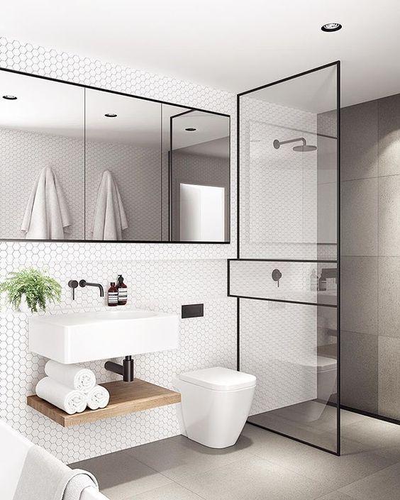 kabina prysznicowa typu walk-in ze ścianką z cienkim czarnym profilem który dzieli ją na trzy części. uzupełnieniem czarne detale w postaci barerii, wylewek oraz czarnej ramy potrójnego lustra