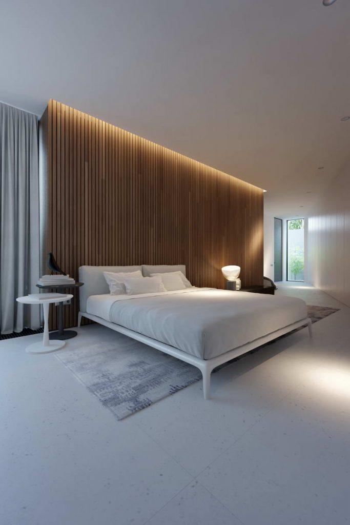 minimalna sypialnia z łożem na tle drewnianych paneli podświetlonych ledami.