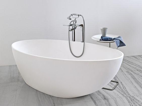 minimalistyczna łazienka z białą wolnostojącą wanną na marmurowej posadzce ze starodawną srebrną baterią w nowoczesnej odsłonie