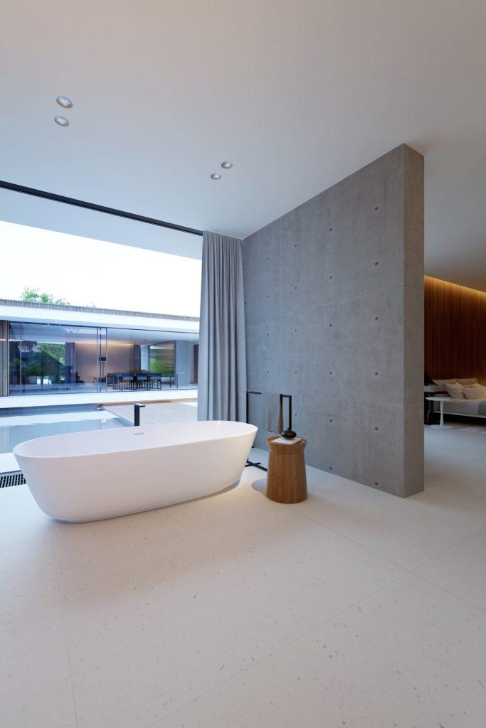 widok na minimalistyczną betonową ściankę działową która częściowo dzieli pomieszczenia łazienkę i sypialnię