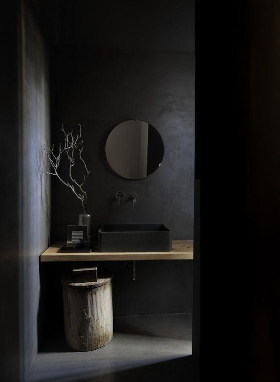 ciemne okrągłe lustro idealnie integruje się z ciemnym wnętrzem łazienki