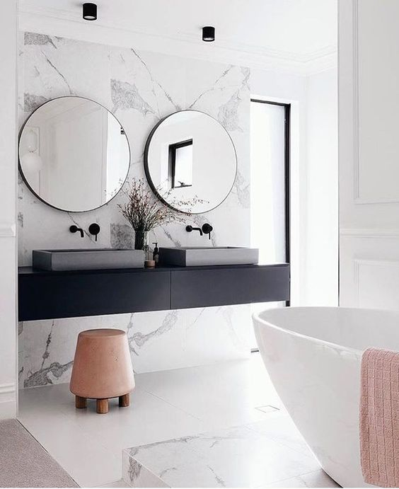 marmurowe ściany i betonowe umywalki, do tego okrągłe lustra w cienkich a głębokich, czarnych ramach, minimalistycznych