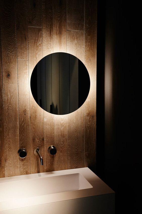 okrągłe lustro bez ramy podświetlone od tyłu daje magiczny efekt w łazience