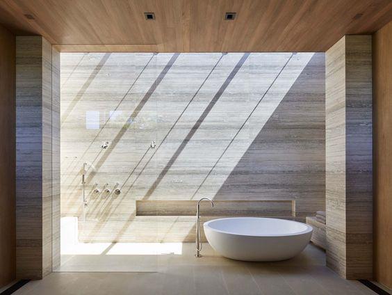 słońce przenikające przez świetlik tworzy wzory na kamiennej ścianie łazienki, pada dokładnie nad niecką prysznicową, można bać prysznic w słońcu