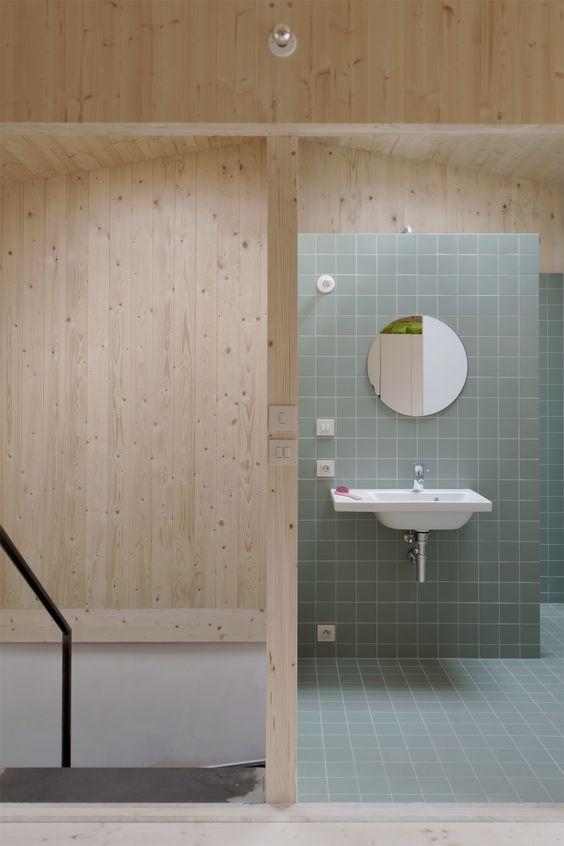 surowe wnętrze łazienki i surowe, okrągłe lustro bez ramy