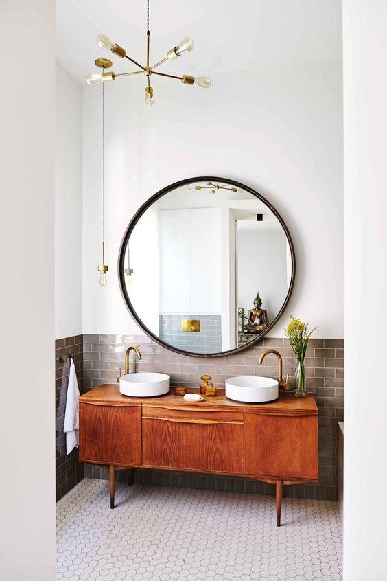 wielkie okrągłe lustro przy dwóch okrągłych umywalkach, przez swą wielkość jest mocnym akcentem łazienki