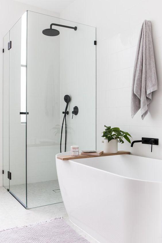 biała łązienka z czarną armaturą i drewnianymi dodatkami w postaci półki na wannę