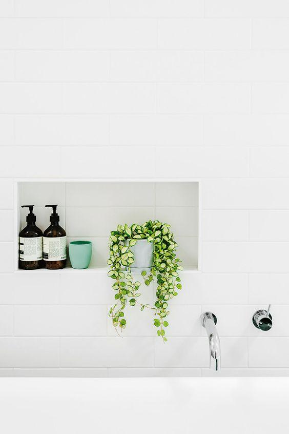 biała łazienka z czarnymi dodatkami i zielenią